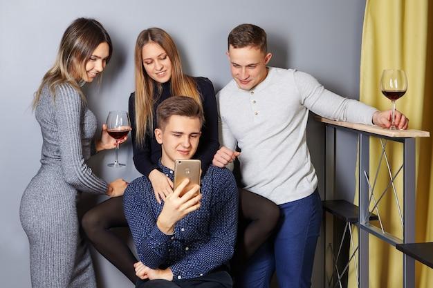 Юноши и девушки старше 20 лет сделали групповое фото на студенческой вечеринке и просматривают его на экране смартфона.