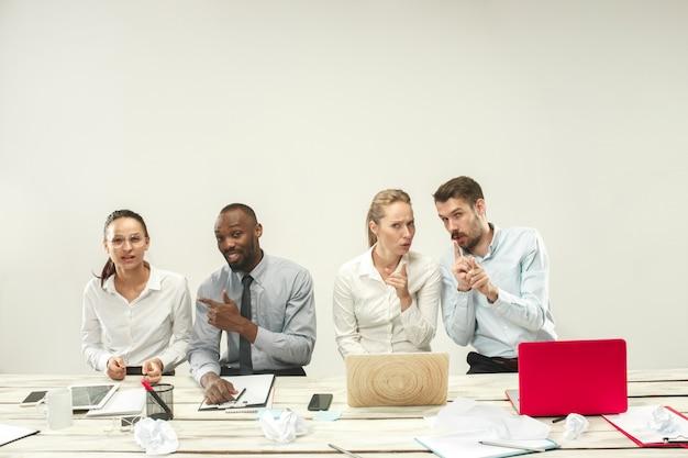 若い男性と女性がオフィスで座っているとラップトップに取り組んでいます。感情の概念