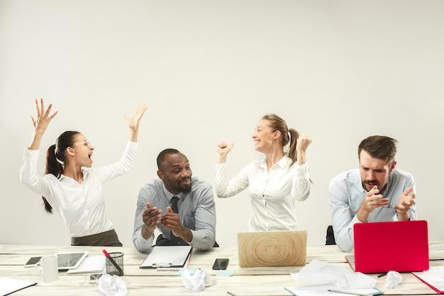 젊은 남성과 여성은 사무실에 앉아 랩톱에서 작업합니다. 감정 개념