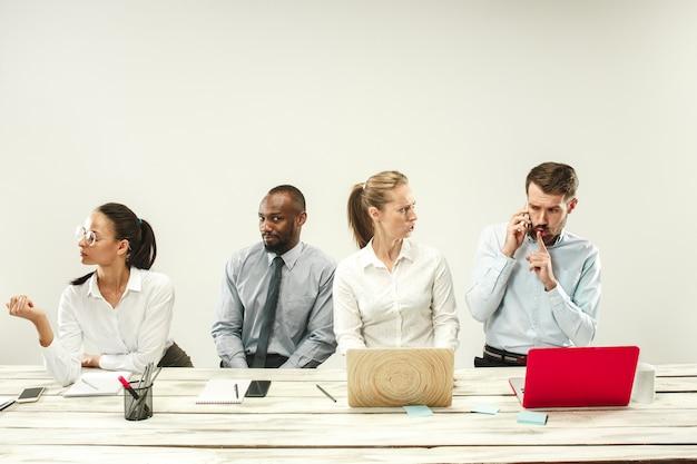 若い男性と女性がオフィスで座っているとラップトップに取り組んでいます。