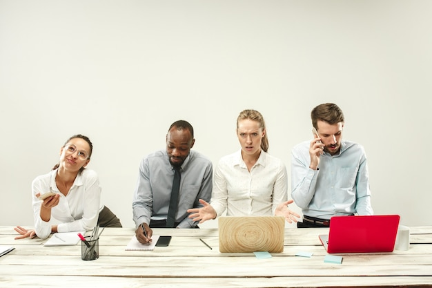 젊은 남성과 여성은 사무실에 앉아 랩톱에서 작업합니다.