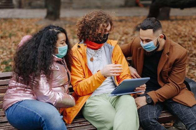 都市公園の木製ベンチに座ってタブレット画面を見ている医療衛生マスクを身に着けている若い男性と女性。友情、技術、コロナウイルスの概念。