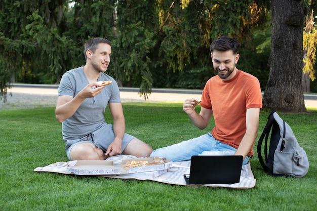 若い男性はおいしいピザを食べ、冗談を言って笑っています。