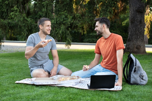 Young men are eating yummy pizza, talking and laughing at jokes. friends sitting on nature outdoors eat pizza on picnic.