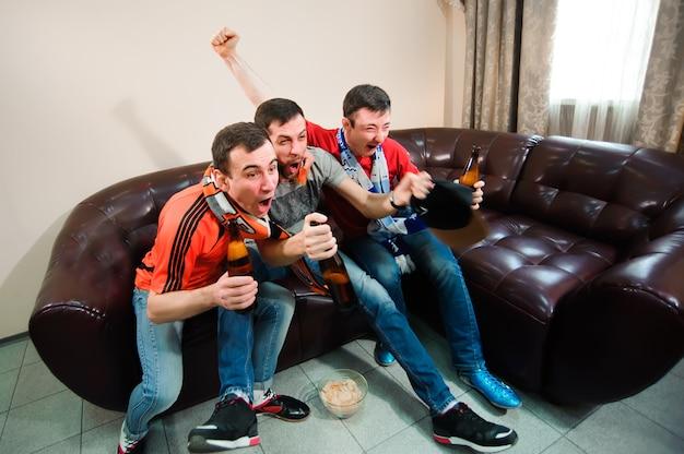 若い男性はビールを飲み、チップを食べ、そしてサッカーのルート
