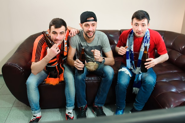 Young men drink beer, eat chips and root for football