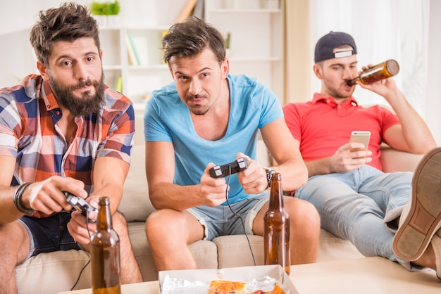 Young men drink beer, eat pizza and play games play station
