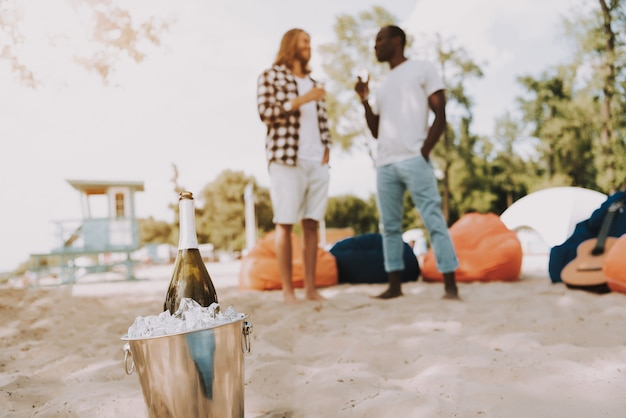 Young men drink champagne bottle in ice bucket.