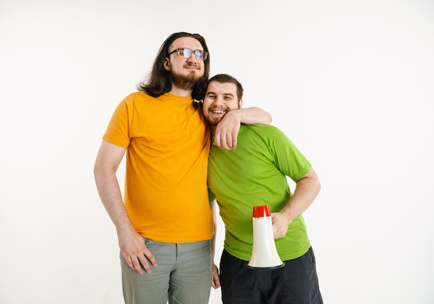 Young men hugging with megaphone on white wall
