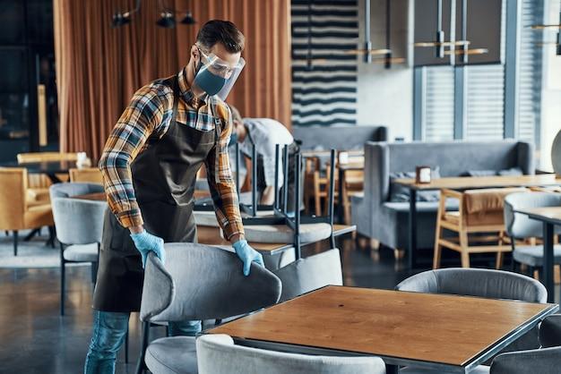 Молодые люди в защитных масках и фартуках расставляют мебель в ресторане