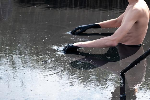 癒しの泥の中の若い男性。有用な泥のあるミネラル塩湖。