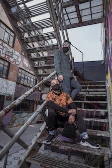 검은 마스크를 쓰고 오래 된 금속 계단에 젊은 남자