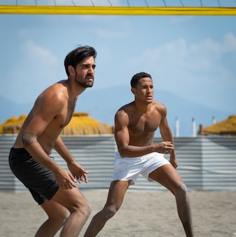 Young men playing beach volleyball on the beach on a sunny day