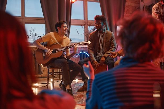Молодые люди играют для своих друзей
