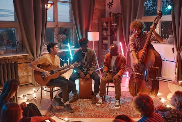 Молодые люди играют на музыкальных инструментах в музыкальной группе, которую они исполняют для людей