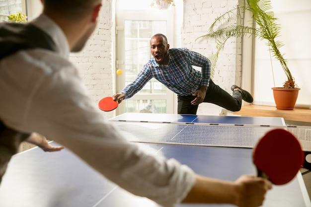 직장에서 탁구를 치는 젊은 남자들. 캐주얼한 옷을 입은 친구들은 화창한 날에 함께 탁구를 칩니다. 여가 활동, 스포츠, 우정, 팀 빌딩, 팀워크의 개념.