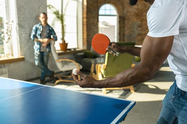 Молодые люди играют в настольный теннис на рабочем месте, развлекаясь