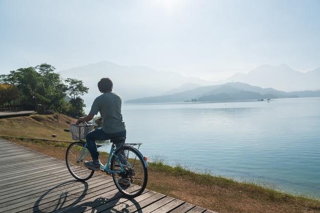朝は湖で自転車道で自転車に乗る若い男性。アクティブな人々。屋外