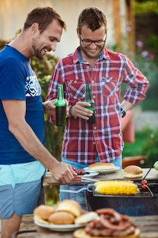 Young men roasting barbecue on grill in cottage countryside.