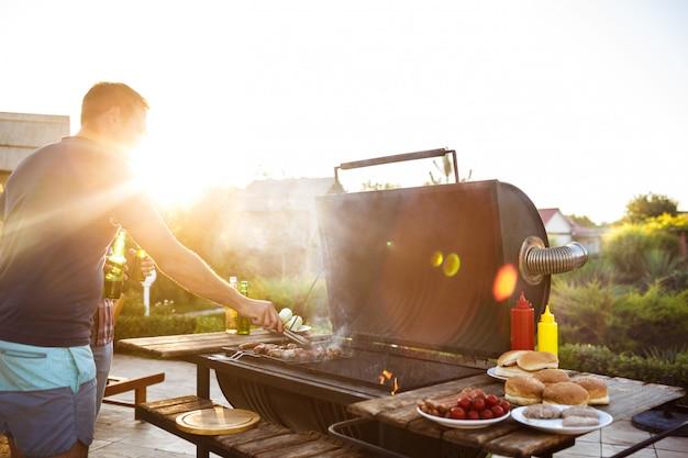 若い男性は、コテージの田舎でグリルでバーベキューを焙煎します。