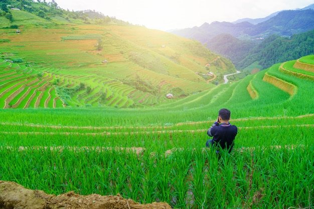 Young men sitting and taking pictures beautiful terraced rice paddy field and mountain landscape