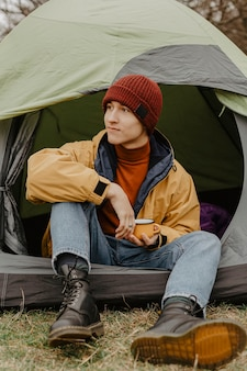 Young men sitting in tent in nature