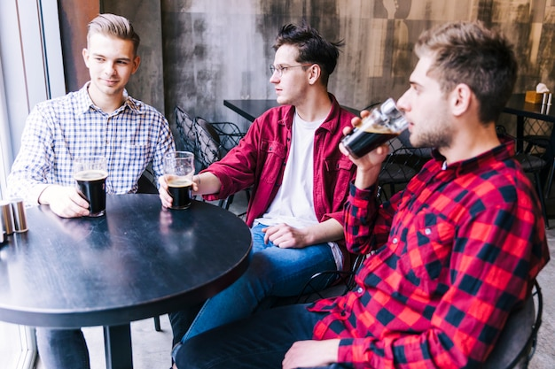 Young men sitting together drinking the beer with his friend