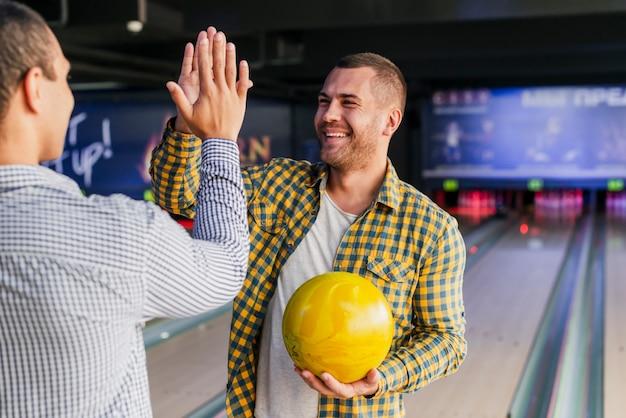 Giovani uomini in piedi in un club di bowling