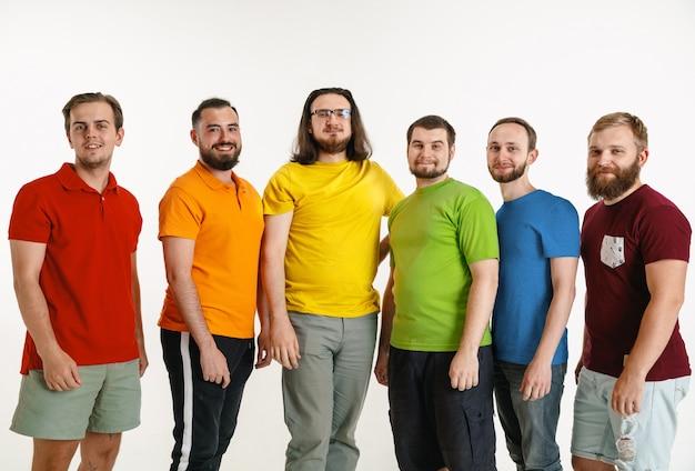 Молодые люди, одетые в цвета флага лгбт, изолированные на белой стене