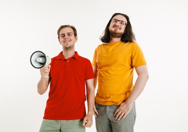 Молодые люди в цветах флага лгбт на белой стене. кавказские модели-мужчины в ярких рубашках. выглядите счастливым, улыбающимся и обнимающимся. концепция гордости, прав человека и выбора лгбт. держа мундштук.