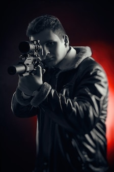 The young men with guns posing on a black background in backlit