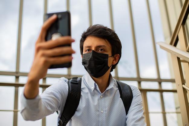 マスクをした若い男性が食事の階段に座っており、携帯電話を手に持ってセルフィーを撮っています。