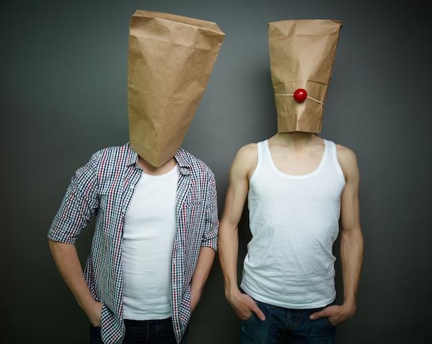 彼らの頭の上に紙袋を持つ若い男性