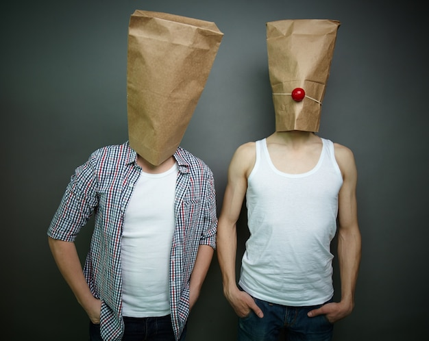 Young men with paper bags over their heads