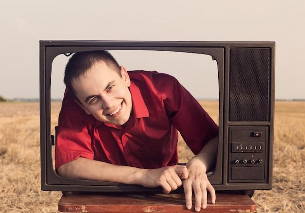 夏のフィールドでヴィンテージテレビを持つ若い男性