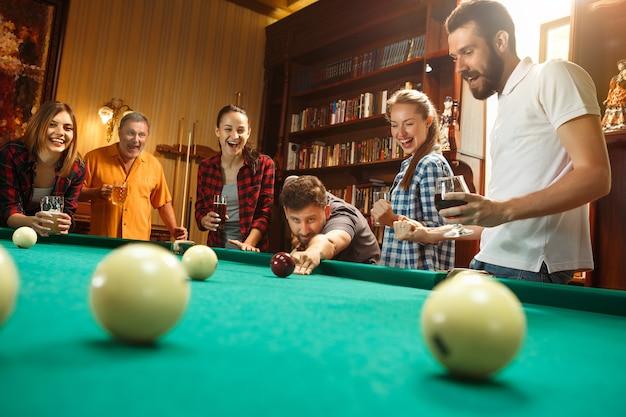 Giovani uomini e donne che giocano a biliardo in ufficio dopo il lavoro.