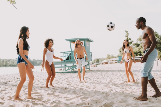 Young men and women playing football on beach