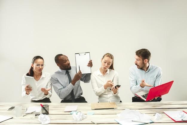 Giovani uomini e donne seduti in ufficio e lavorando su laptop. concetto di emozioni