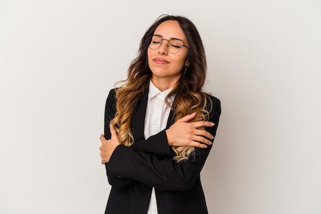 白い背景で隔離の若いメキシコのビジネス女性は、のんびりと幸せに笑って抱擁します。