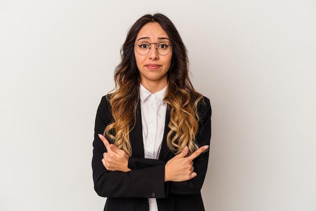 Молодая мексиканская деловая женщина, изолированная на белом фоне, указывает боком, пытается выбрать один из двух вариантов.