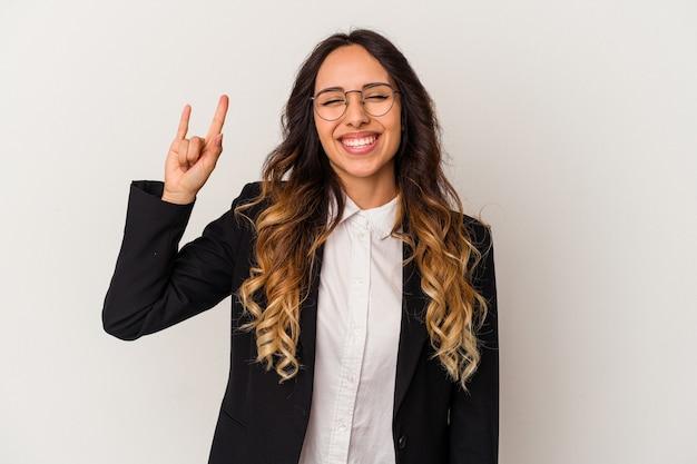 혁명 개념으로 뿔 제스처를 보여주는 흰색 배경에 고립 된 젊은 멕시코 비즈니스 여자.