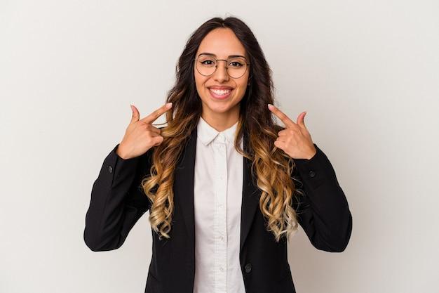 입에서 손가락을 가리키는 흰색 배경 미소에 고립 된 젊은 멕시코 비즈니스 여자.