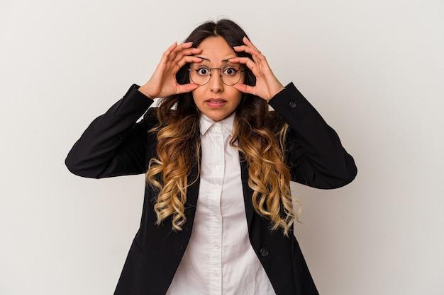 Молодая мексиканская бизнес-леди изолирована на белой стене, держа глаза открытыми, чтобы найти возможность успеха.