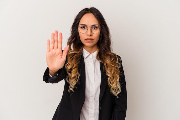 一時停止の標識を示す伸ばした手で立っている白い壁に孤立した若いメキシコのビジネス女性は、あなたを防ぎます。