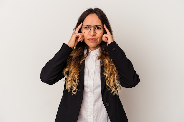Young mexican business woman isolated on white background focused on a task, keeping forefingers pointing head.