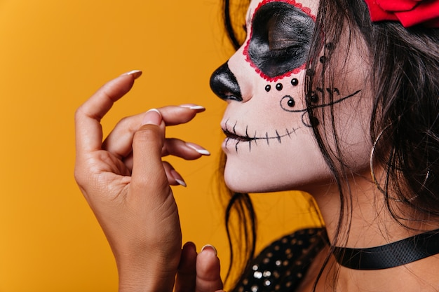 Young mexican girl with roses in her hair and skull-shaped art on face poses cute with her eyes closed