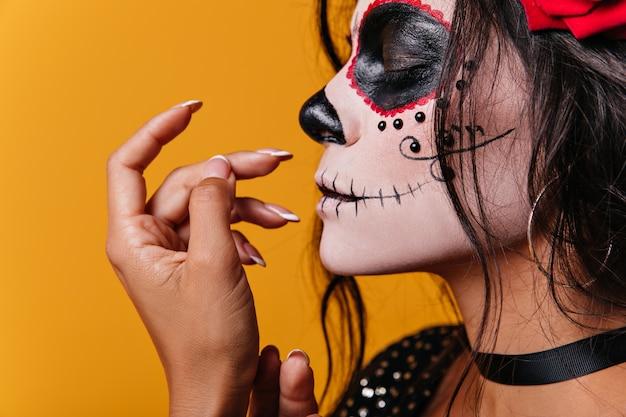 彼女の髪にバラと顔に頭蓋骨の形をしたアートを持つ若いメキシコの女の子は目を閉じてかわいいポーズをとる