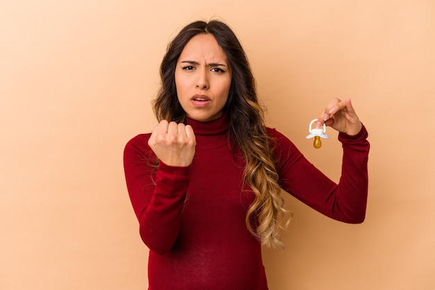 Young mexican pregnant woman holding pacifier isolated on beige background showing fist to camera, aggressive facial expression.