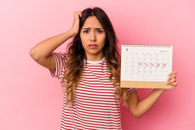 ピンクの背景に隔離されたカレンダーを持つ若いメキシコ人女性がショックを受け、重要な会議を思い出した。