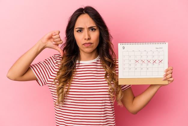싫어하는 제스처, 엄지 손가락을 보여주는 분홍색 배경에 고립 된 달력을 들고 젊은 멕시코 여자. 불일치 개념.